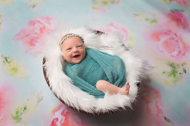 Newborn baby girl smiling on floral background